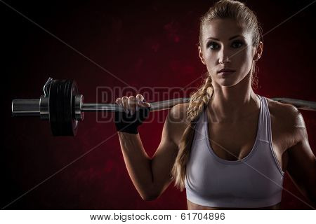 Brutal athletic woman pumping up muscles with barbell on red background