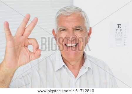 Portrait of a smiling senior man gesturing ok with eye chart in the background at medical office