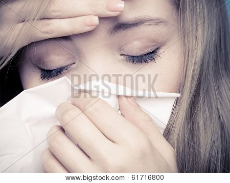 Flu cold or allergy symptom. Closeup of sick young woman girl with fever sneezing in tissue. Health care. Studio shot. Black and white photo. poster