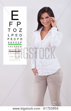 Woman Pointing Standing Nex To An Eye Chart