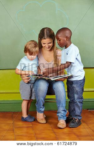 Nursery teacher and children reading a book together in kindergarten