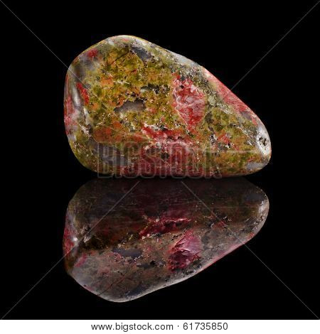 Mineral Unakite with reflection on black surface background