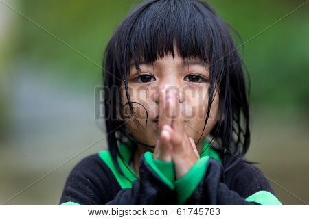 BANAUE, PHILIPPINES, DECEMBER 04 : A young unidentified Filipino little girl is praying under the rain in the village of Banaue, north Luzon, Philippines, on december 04, 2013