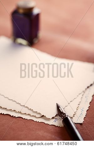 vintage ink pen, inkpot and retro photographs on leather table, shallow dof