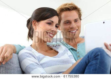Couple in sofa websurfing on internet with tablet