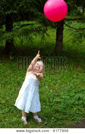 Pretty Little Girl Playing With Red Balloon In The Forest.