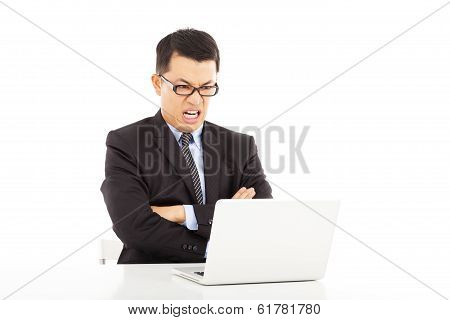 Angry Businessman Looking At Laptop with Crossed Arms