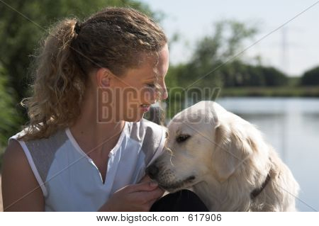 Beautiful blond woman out by the waterside with her dog poster