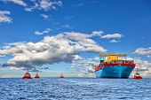 Tugboat assisting container cargo ship to harbor. poster