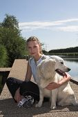 Pretty blond woman relaxing with her dog by the waterside poster