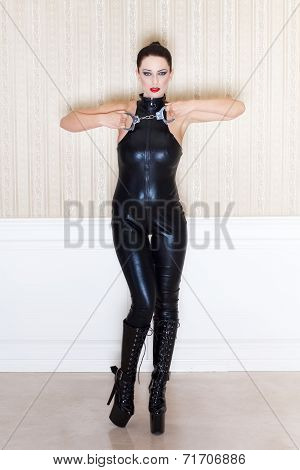 Brunette sexy woman in latex catsuit showing handcuffs bdsm poster