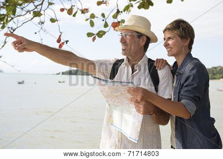 Sightseeing: Middle aged couple on vacation search the way with map