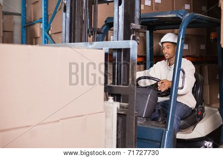 Forklift driver operating machine with boxes on it in a large warehouse