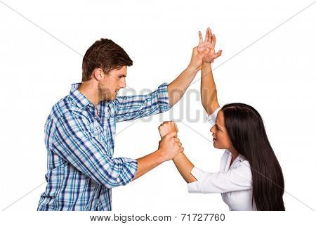 Aggressive man overpowering his girlfriend on white background