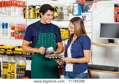 Happy woman holding screwdriver set with worker swiping credit card at hardware store