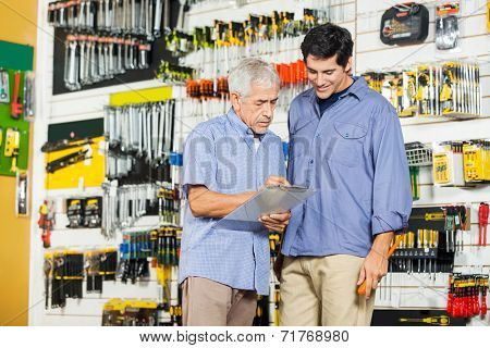 Father and son checking checklist on clipboard in hardware store