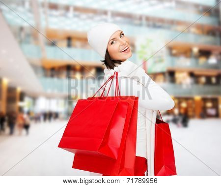 happiness, winter holidays, christmas and people concept - smiling young woman in white hat and mittens with red shopping bags over shopping center background