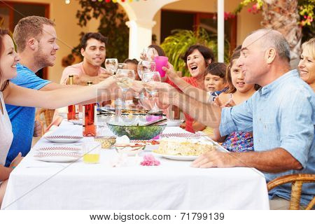 Large Family Group Celebrating Birthday On Terrace Together