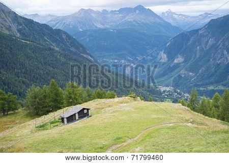 COURMAYEUR, ITALY - AUGUST 29: High angle view of chalet with Courmayeur valley in the background. The area is a stage of the popular Mont Blanc tour. September 29, 2014 in Courmayeur.