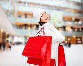 happiness, winter holidays, christmas and people concept - smiling young woman in white hat and mittens with red shopping bags over shopping center background poster