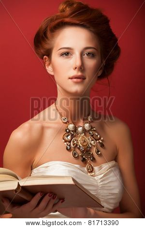 Portrait Of Redhead Edvardian Women With Book On Red Background.