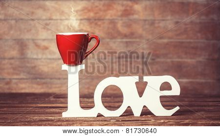 Tea Or Coffee Cup With Word Love On Woodent Table.