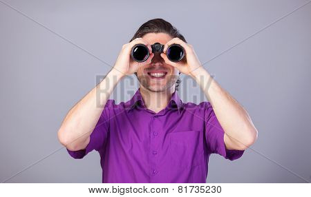 Handsome Man With Binocular On Gray Background.