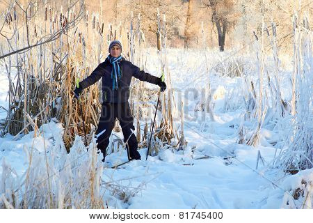 Boy cross country skiing in forest at sunny winter day