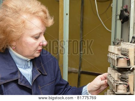 Operator woman-engineer in machine room (elevator) check the mechanical relay and cabinet. poster