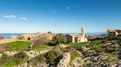Ruined buildings and the restored church in the abandoned village of Occi near Lumio in the Balagne region of Corsica poster