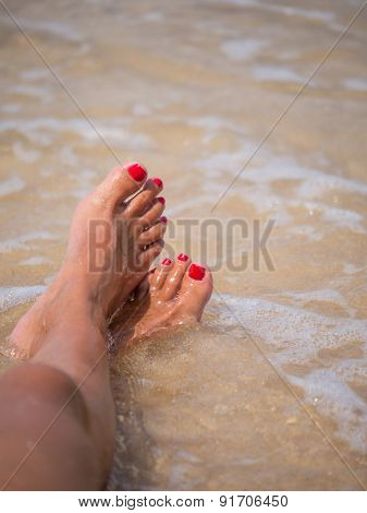 Tanned feet with pedicure  and the turquoise sea and blue sky