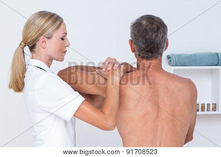Doctor examining her patient shoulder in medical office poster