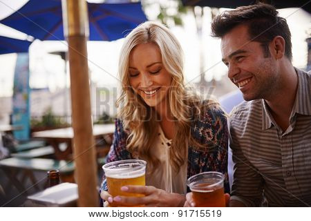 couple drinking beer at outdoor bar shot with selective focus