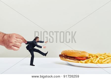 small man running to junk food but the big hand holding him over light grey background