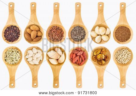 superfood grain, seed, berry, nuts and garlic abstract - top view of isolated on white wooden spoons (two rows)