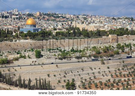 The ancient Jewish cemetery on the Mount of Olives on the background of the old quarters of Jerusalem. Seen the Golden Dome Mosque Dome of the Rock
