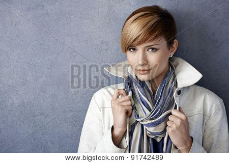 Closeup portrait of beautiful young woman wearing jacket and scarf