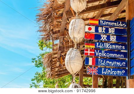 Welcome sign in different languages on beach