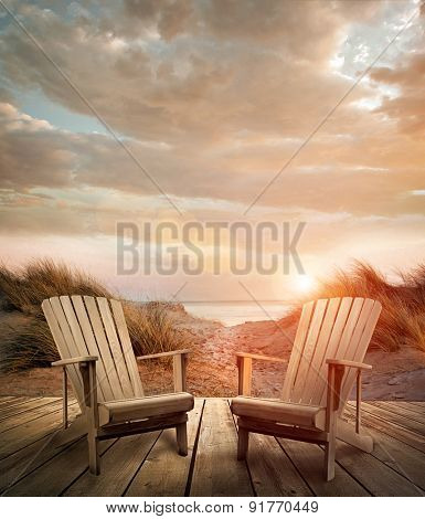 Wooden deck with chairs, sand dunes and ocean in background