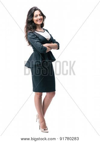 Full length portrait of a smiling businesswoman standing with arms folded and looking away