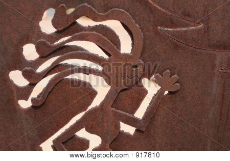 Metal Worked Image Of Running Kokopelli Man That Is Rusty
