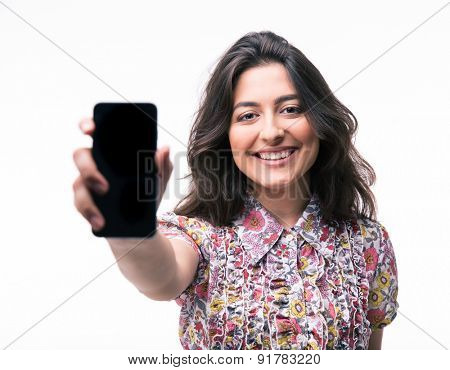Young woman showing blank smartphone screen isolated on a white background. Looking at camera