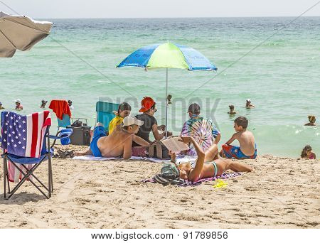 People Enjoy The Beautiful Beach At Sunny Isles Beach