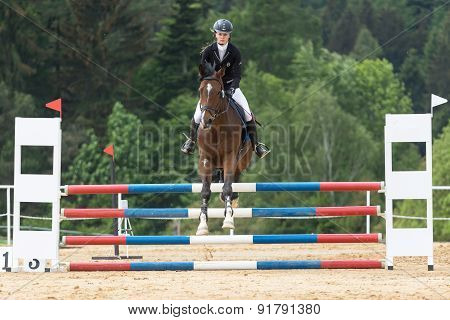 Front View Of Beautiful Young  Horsewoman Jumping
