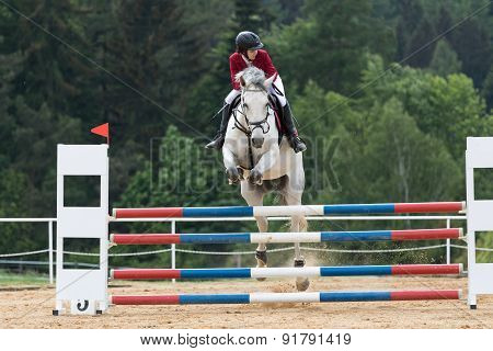 Young Horsewoman In Red Jacket On A White Horse