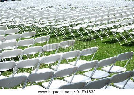 Rows and rows of white foldup chairs set out facing one way as an auditorium on grass for a concert