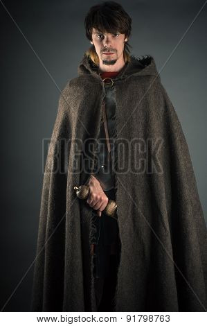 wandering man in woolen cape with a sword