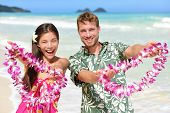 Hawaii welcome - Hawaiian people showing leis flower necklaces as a welcoming gesture for tourism. Travel holidays concept. Asian woman and Caucasian man on white sand beach in Aloha clothing. poster