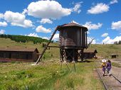 children walking toward a water tower on the old cumbres & toltec rail line. poster