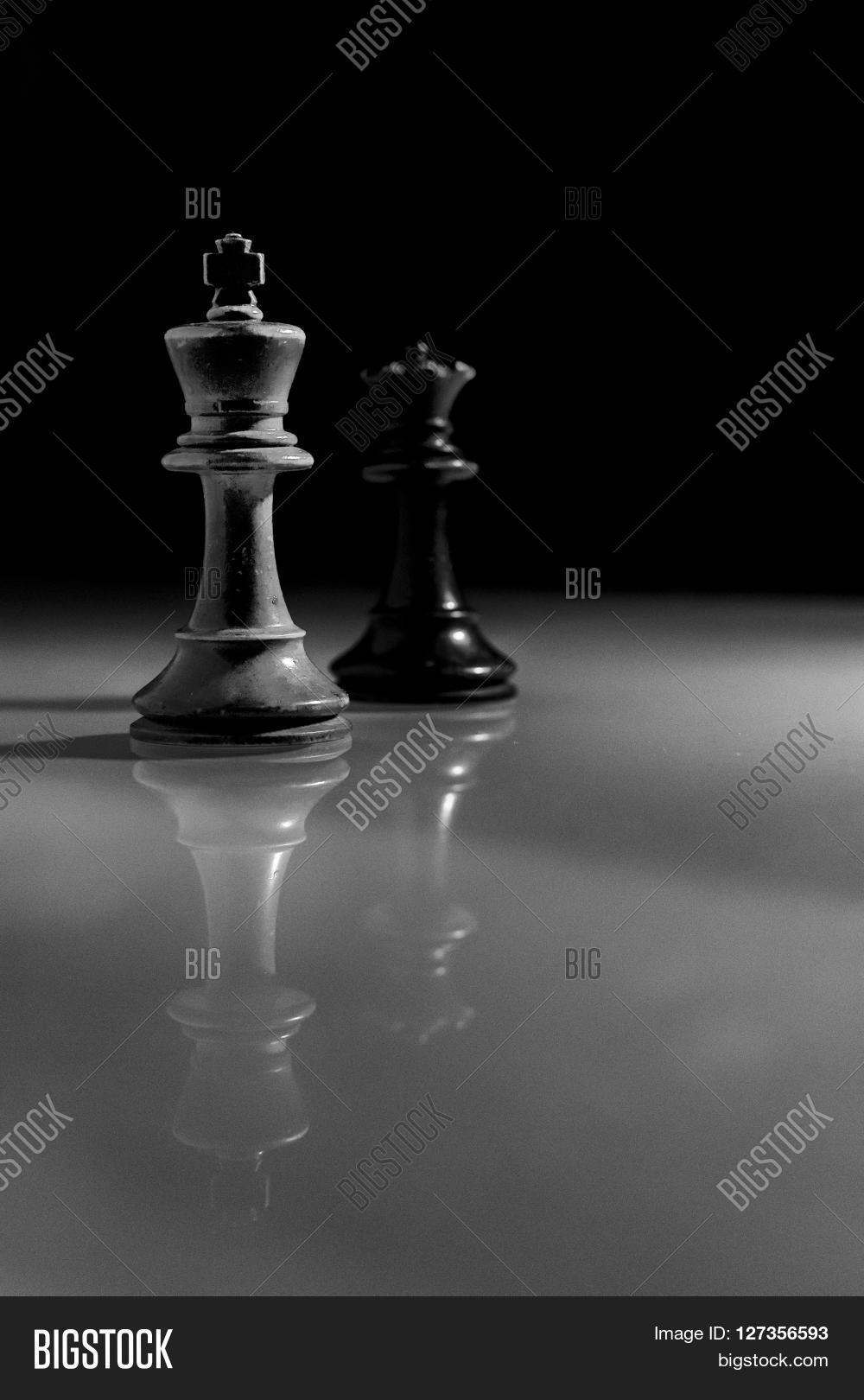 White king and black queen chess piece reflection